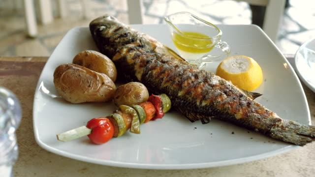 grekisk mat. närbild av stekt fisk med grönsaker på en vit tallrik. grekland. 4k - tallrik uppätet bildbanksvideor och videomaterial från bakom kulisserna