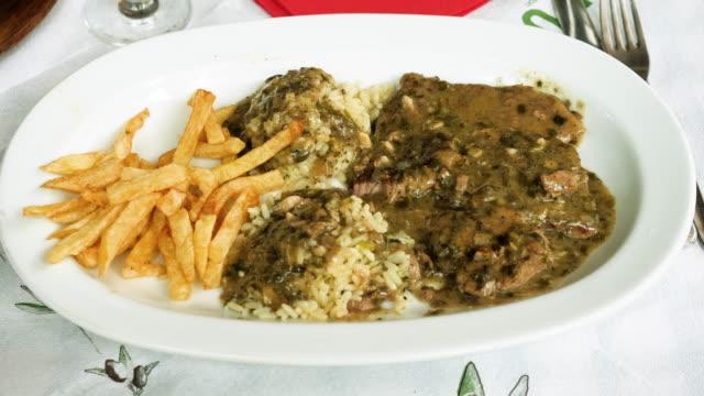 grekisk mat. pommes frites, vitt ris och sås med rostat lamm. 4k (4k) - tallrik uppätet bildbanksvideor och videomaterial från bakom kulisserna