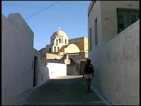 isole greche: turista cammina attraverso il villaggio tradizionale - isole egee video stock e b–roll