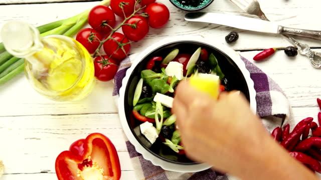 Greek salad preparation process: a cook squeezes lemon to add lemon juice video