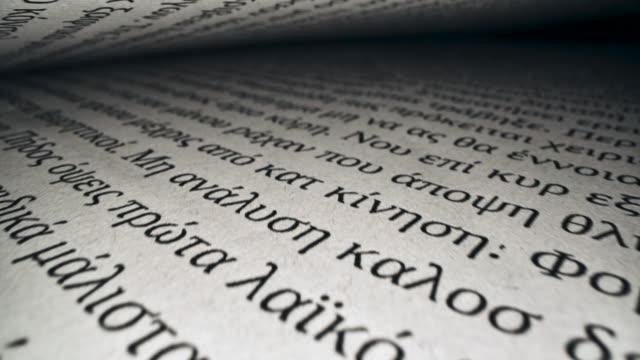 stockvideo's en b-roll-footage met grieks manuscript op de pagina's van een open boek - heilig geschrift