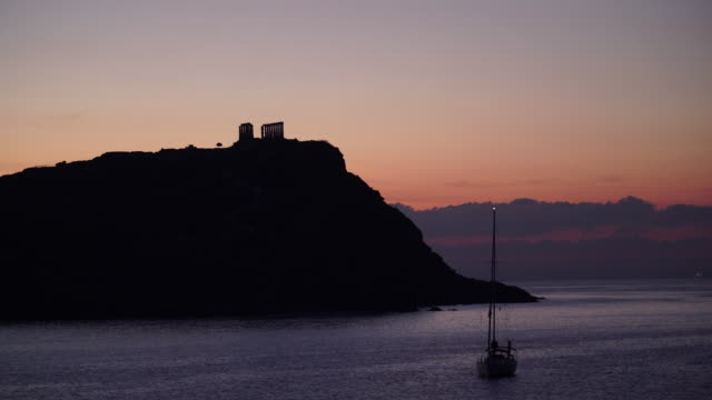 Greek temple of Poseidon at morning, Cape Sounio Seascape of the Aegean sea, yacht on water surface. Great early morning view of the Temple of Poseidon, Cape Sounio, Greece Europe sounion stock videos & royalty-free footage