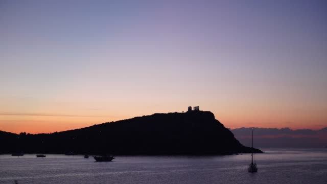 Greek temple of Poseidon at morning, Cape Sounio Seascape of the Aegean sea, yacht on water surface. Great early morning view of the Temple of Poseidon, Cape Sounio, Greece Europe. sounion stock videos & royalty-free footage