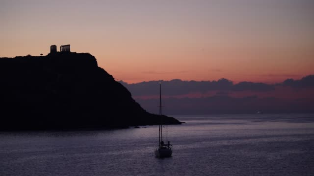 Greek temple of Poseidon at sunrise, Cape Sounio Seascape of the Aegean sea, yacht on water surface. Great morning view of the Temple of Poseidon at sunrise, Cape Sounio, Greece Europe. Time lapse sounion stock videos & royalty-free footage