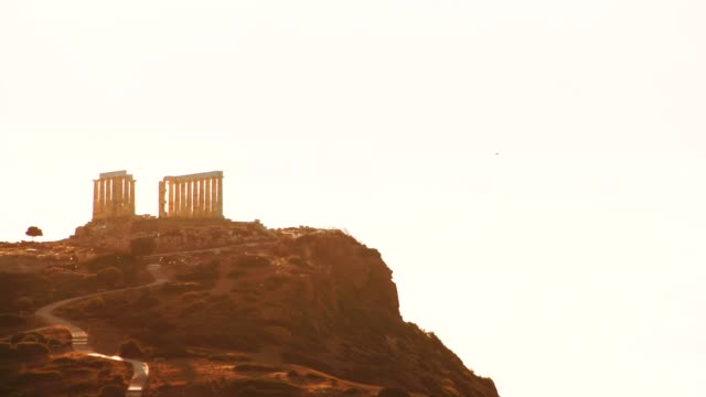 Greek temple of Poseidon, Cape Sounio Greece Cape Sounion. Ruins of an ancient temple of Poseidon at morning light with flock of birds flying over hill 4K sounion stock videos & royalty-free footage
