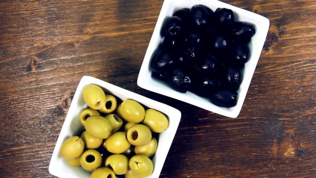 green and black olives on square bowl on wood - oliva video stock e b–roll