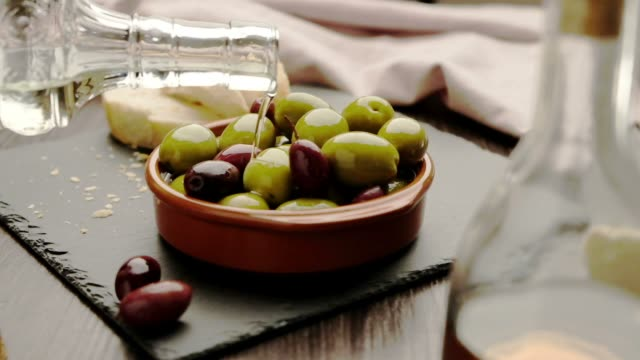 green and dark olives on a brown greek plate. olive oil. - oliva video stock e b–roll