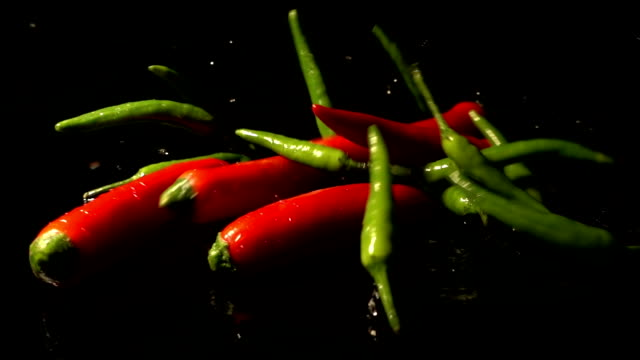 Green And Red Chilies Falling And Splashing video