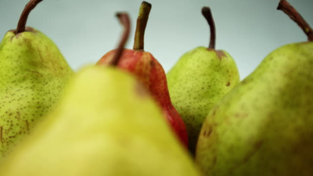 Green and red pears rotate and come into view. Locked down macro shot of green and read pears on rotating plate. pear stock videos & royalty-free footage