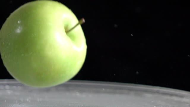 Green apple falling on glass, slow motion video
