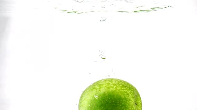 green apple slowly immersed in water. video in slow motion. isolated fruit on white background. - soczysty filmów i materiałów b-roll