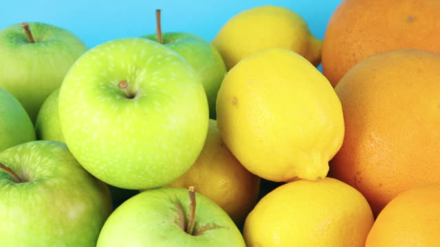green apples, lemons, oranges, strawberries, coconut and kiwi close up on blue background - icon set healthy video stock e b–roll
