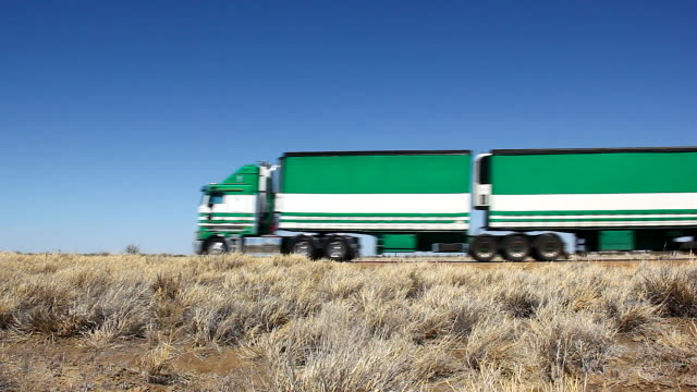 Green big truck with four trailers passing by empty road in Outback Australia