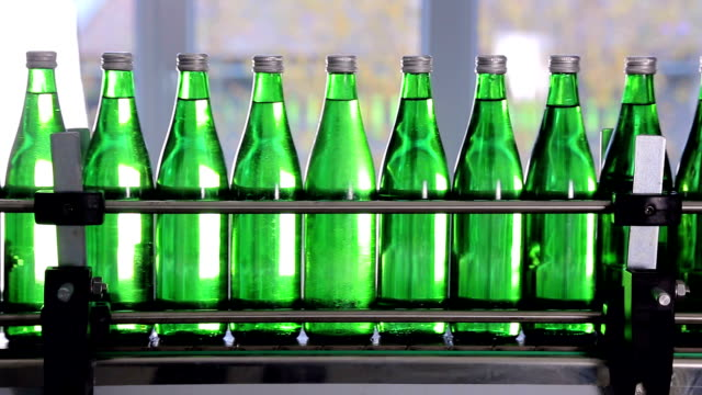 green bottles for mineral water are moving along the automatic production line. video