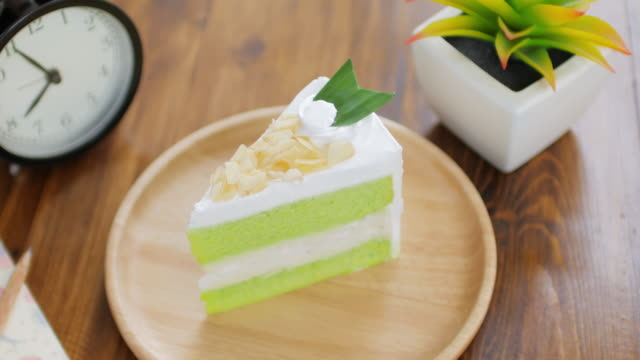 Green Cake Matcha green tea cream cake on wooden table for relax time , dolly shot right to left video