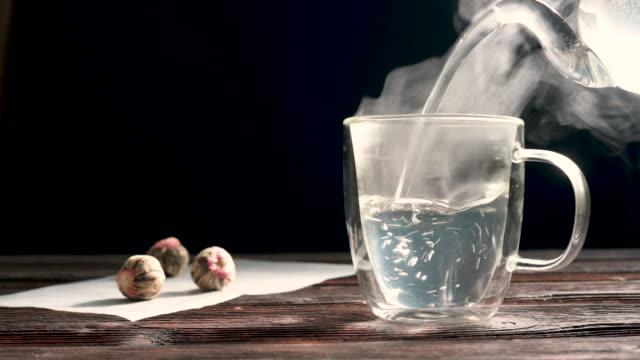 bocciolo di fiori di tè cinese verde che fiorisce in tazza di tè di vetro. - teiera video stock e b–roll