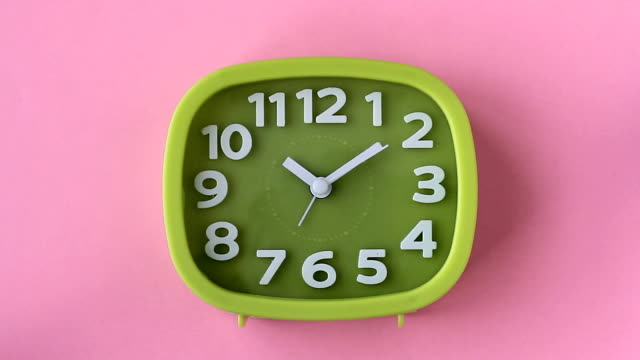 green clock with white numbers and arrows on pink background, time lapse - clock стоковые видео и кадры b-roll