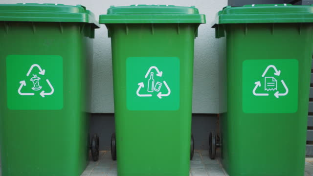 Green colored, plastic garbage bins, with different recycle logos on front, stacked in row against brown wood wall. Concept of waste sorting for food, paper and bottles. Saving Environment from Trash.