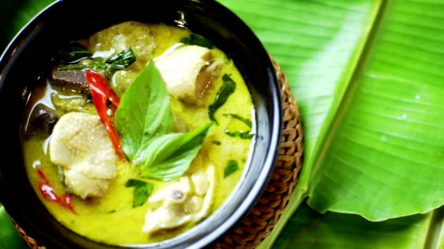 green curry with chicken in black bowl served on banana leaf, thai cuisine. - thai food stock videos and b-roll footage