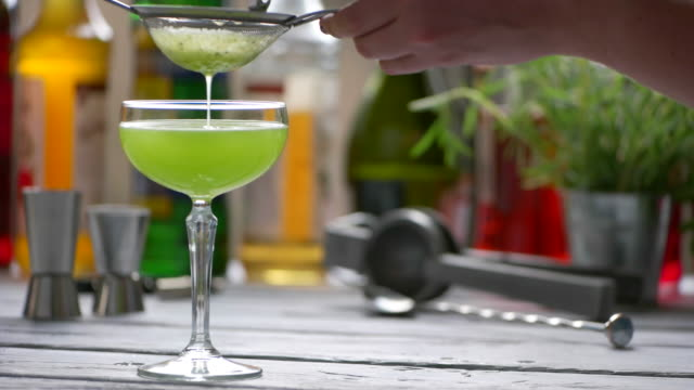 Green drink drips through sieve. video