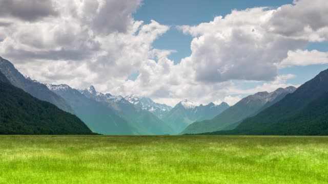 green field and mountain blue sky - grass stock videos & royalty-free footage