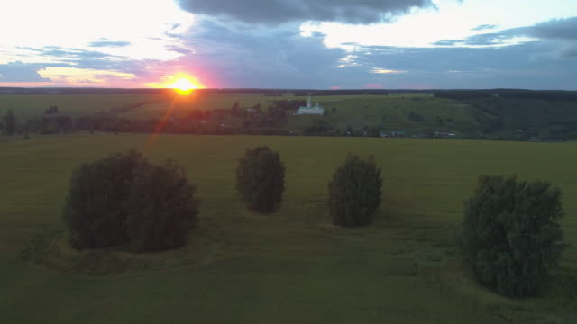 green field with trees and church at sunset. aerial view. - monti urali video stock e b–roll