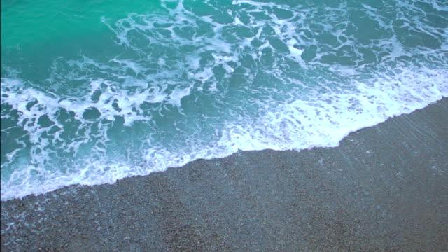 vídeos de stock e filmes b-roll de verde espumosa oceano ondas entrar em terra, salpicos na praia de areia em câmara lenta - maré