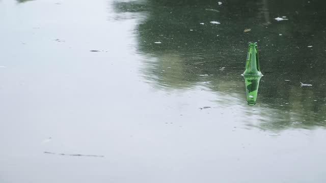 Green glass bottle floating in water
