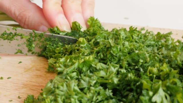 Green healthy vegetable  parsley smaller pieces 4K 3840X2160 UltraHD  footage - Petroselinum crispum plant on cutting board 4K 2160p UHD video