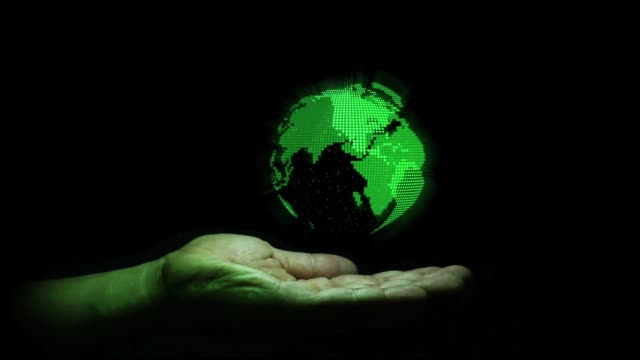 Green hologram the earth shape rotation on human hand with black background , technology for future concept