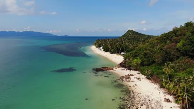 海の近くの緑のジャングルとストーニービーチ。サムイ島の白い砂浜の穏やかな青い海の近くの熱帯雨林と岩, タイ.ドリームビーチドローンビュー。リラックスして休日のコンセプト。 - サムイ島点の映像素材/bロール