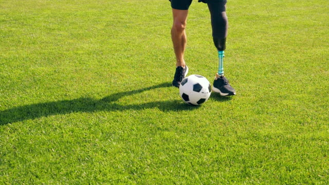 Green lawn with a ball getting kicked by a disabled man Green lawn with a ball getting kicked by a disabled man. HD prosthetic equipment stock videos & royalty-free footage