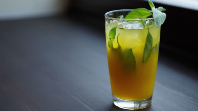 green lemon cocktail drink served with mint leaves and ice - gusto aspro video stock e b–roll