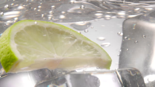 Green lemon slice falling down in water with ice cubes in it