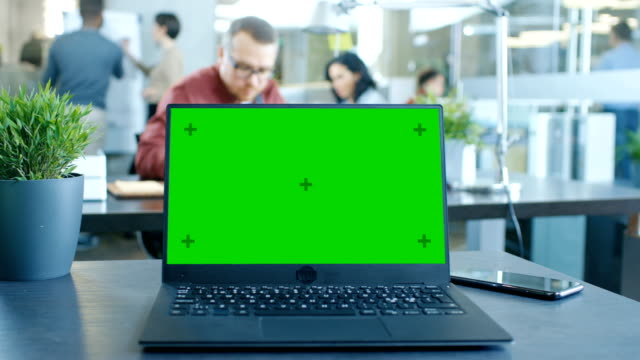 green mock-up screen laptop on the table. in the background creative young professionals working in the modern office. - scrivania video stock e b–roll