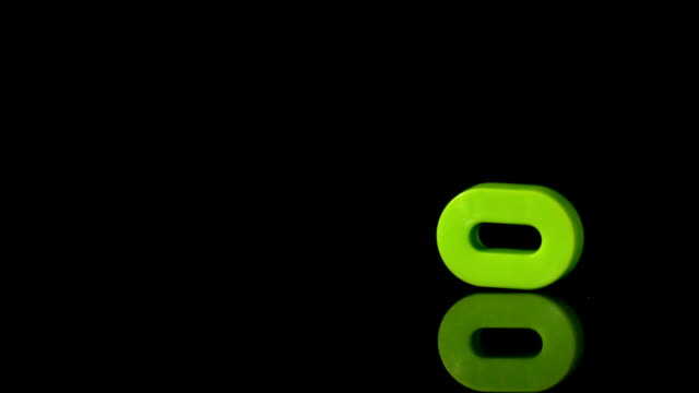 Green number zero falling on black background video