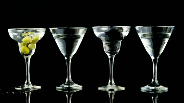 stockvideo's en b-roll-footage met groene olijven wegvalt in vier cocktail glazen - martiniglas
