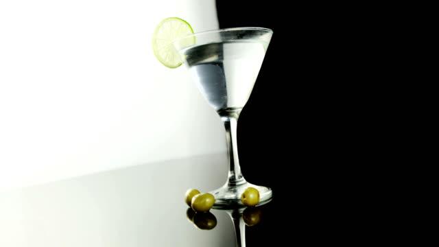 stockvideo's en b-roll-footage met groene olijven vallen in het cocktailglas - martiniglas