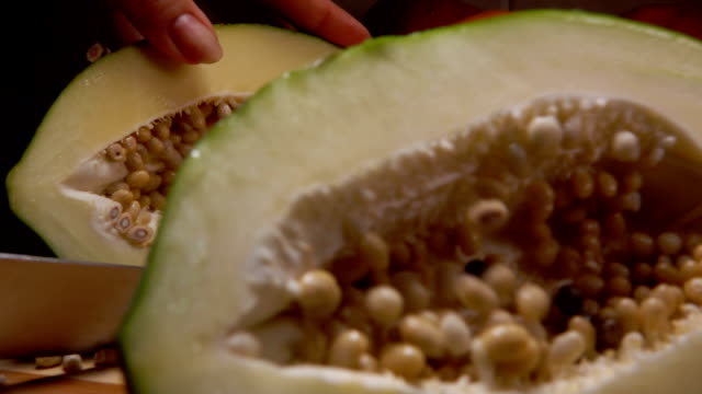 Green papaya cut in a halves with a knife - video