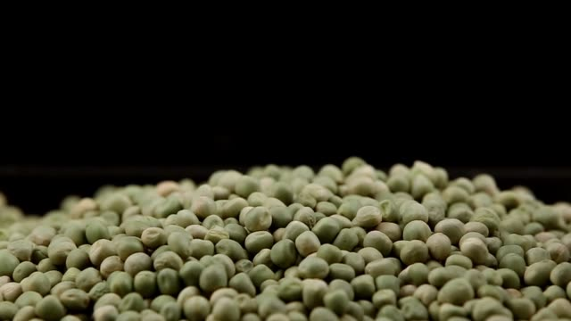 Green peas falling isolated in black background taken with sliding camera video