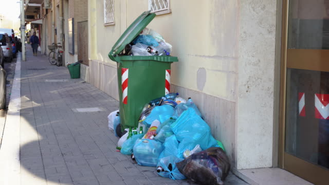 Green plastic container is overfilled with trash and organic waste on the street of Ladispoli, Italy. People throwing out garbage on the ground under the windows of residential building. Trash problem in Rome Green plastic container is overfilled with trash and organic waste on the street of Ladispoli, Italy. People throwing out garbage on the ground under the windows of residential building. Trash problem in Rome dumpster fire stock videos & royalty-free footage