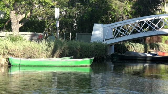 vídeos y material grabado en eventos de stock de un bote de remos verde atado por un puente en un canal - anclado