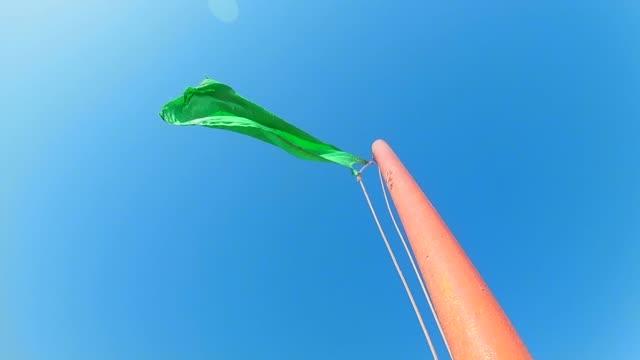 푸른 맑은 하늘에 대한 깃대에 흔들리는 녹색 안전 플래그. 슬로우 모션 타임랩스. - saudi national day 스톡 비디오 및 b-롤 화면