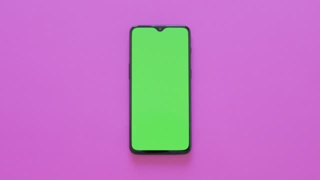 vídeos de stock e filmes b-roll de green screen - a modern smartphone lies on pink background - modelo arte e artesanato