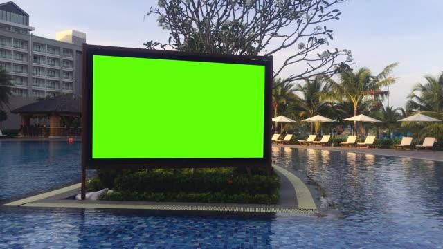 vídeos de stock, filmes e b-roll de quadro de avisos verde da tela no estágio do hotel perto da área sunbathing. viagem de luxo de verão - pré estreia