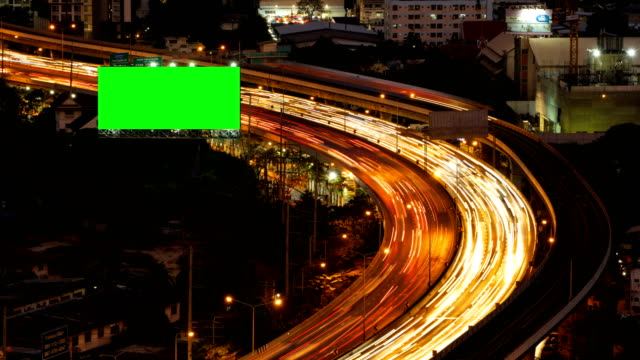 Green screen billboard with traffic jam on road at highway for advertising in urban city, Bangkok , Thailand at night.