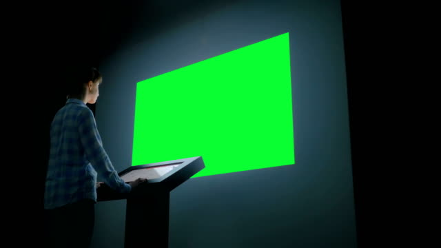 Green screen chroma key concept - woman looking at empty large wall display