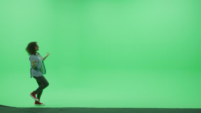 Green Screen Chroma Key Studio: Beautiful Teenage Girl Wearing Stylish Casual Clothes Dances Across Room