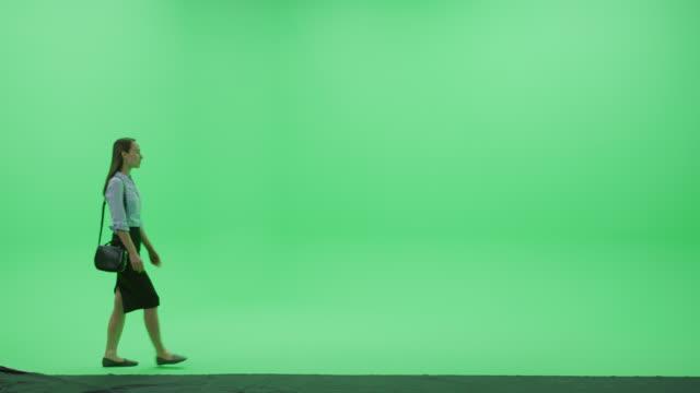 グリーンスクリーンクロマキースタジオ:スタイリッシュなカジュアルスカートとニースバッグを身に着けている美しい若い笑顔の女性は、部屋を横切って歩きます。サイドビューカメラショ - スタイリッシュ点の映像素材/bロール
