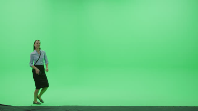 Green Screen Chroma Key Studio: Beautiful Young Smiling Woman Wearing Stylish Casual Skirt Holds Her Smartphone and Dances Happily Across Room. Side View Camera Shot video